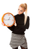 Calm smiling woman with big orange clock gesturing no rush, enough time to be punctual. stock photo