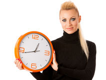 Calm smiling woman with big orange clock gesturing no rush, enough time to be punctual. stock photography