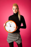 Calm smiling woman with big orange clock gesturing no rush, enough time to be punctual. royalty free stock photos