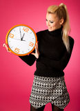 Calm smiling woman with big orange clock gesturing no rush, enough time to be punctual. stock image