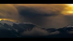 Calm Before the Snowstorm 2.5d. Mountain peaks covered in snow and fast moving clouds moments before a new snowstorm unleashes stock video