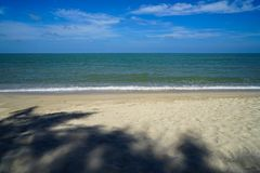 Calm soft foam sea wave on white sandy beach with tree shade and blue sky background. Samila beach, Songkhla, Thailand Royalty Free Stock Photography