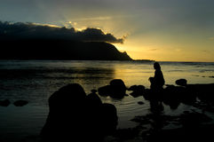 Calm Soul. Woman sits on rocks in the bay as the sun sets behind the mountain.  Rays of sunset splash against blue sky.  Colors are reflected on the waters Stock Photography