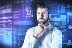 Calm specialist looking thoughtful and touching his beard. How interesting. Clever calm experienced programmer thoughtfully touching his beard while looking Stock Image