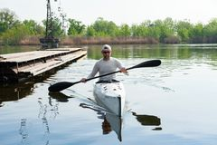 Calm sports man sitting in canoe and holding paddle. River rafting sport concept. Man with kayak and paddle moored to the shore and looking at camera stock photo