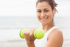 Calm sporty woman lifting dumbbells smiling at camera Royalty Free Stock Image