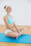 Calm sporty woman sitting on blue exercise mat meditating. With eyes closed stock photo
