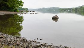 A calm and still Coniston water with a boulder in close focus. Takes from the pebble lined banks of Coniston Water, a lake in the English Lake District. Trees stock image