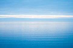 Calm and still open sea blurring into a blue sky Royalty Free Stock Photo