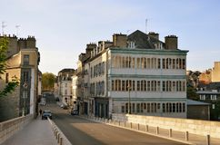 Calm street in the old part of the French city Pau. The traditional townhouses, a passerby and two cars are in the empty street of the historical part in the Royalty Free Stock Photography