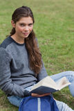 Calm student holding a book while sitting Royalty Free Stock Photos