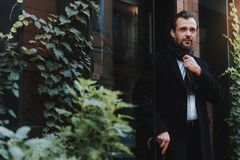 Calm stylish man in black coat is going out. Serene bearded male is walking out of building. He is wearing classic clothes and holding umbrella. Copy space in royalty free stock image