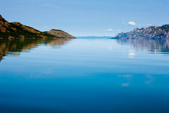 Calm summer day on huge Lake Laberge Yukon Canada. Wide expanse of mirror like calm water surface of huge Lake Laberge, Yukon Territory, Canada, on beautiful stock photography