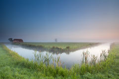 Calm summer misty morning over river Stock Photos