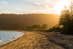 Calm sunny beach with sunset in background Stock Photography