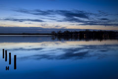 Calm sunrise over a lake with clouds reflection in Royalty Free Stock Photos