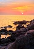 Calm sunrise over the sea shore. Warm and calm sunrise over the rocky sea shore with huge boulders Royalty Free Stock Photos