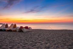 Calm sunrise at sea beach with boats. Calm sea waves touch sandy beach with few boats at sunrise stock photography