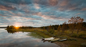 Calm Sunset in Swedish Lapland. Boats at the Shore of a Calm River during Sunset in Swedish Lapland Royalty Free Stock Image
