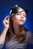 Calm teen girl with a colander on her head Stock Photography