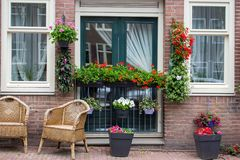 Free Calm Terrace With Chairs And Flower Pots. Exterior Of Unknown Brick Building In Amsterdam, Netherlands. Entrance With Flowers. Stock Photography - 152766822