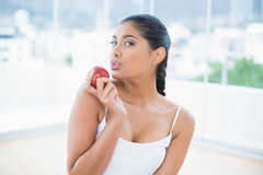 Calm toned brunette holding apple Royalty Free Stock Images
