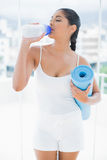 Calm  toned brunette holding sports bottle and exercise mat Stock Images