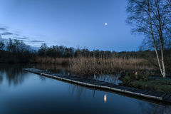 Calm tranquil moonlit landscape over lake and jetty Stock Photography