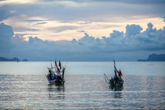 Calm tropical sunset in the background boats. Royalty Free Stock Images