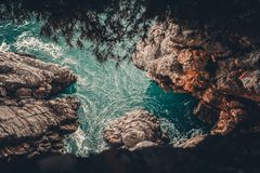 Calm turquoise water with waves and rocks Stock Photography
