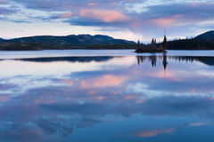 Calm Twin Lakes at Sunset, Yukon Territory, Canada. Calm lake reflecting sky at sunset, Twin Lakes, Yukon Territory, Canada royalty free stock image