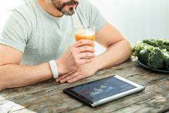 Calm unshaken man sitting and drinking juice. Time to rest. Calm unshaken concentrated man sitting in the bright room by the table using the laptop and drinking Royalty Free Stock Image
