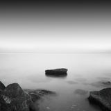 Calm water. Black & white daytime long exposure rocky seascape  with beautiful sky and sea. Black sea, Odessa, Ukraine Stock Photography