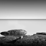 Calm water. Black & white daytime long exposure rocky seascape  with beautiful sky and sea. Black sea, Odessa, Ukraine Royalty Free Stock Photos