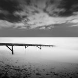 Calm water. Black & white daytime long exposure seascape with beautiful sky and objects in the sea. Black sea, Odessa, Ukraine Royalty Free Stock Photography