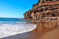 Calm water and blue sky in rustical beach Tiritaña. Bay framed. By high cliffs in barranco near Taurito/Mogan Stock Photos