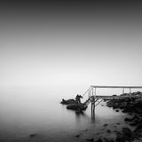 Calm water. Daytime long exposure seascape with object in the sea. The photo taken in black and white. Black sea, Odessa, Ukraine Royalty Free Stock Photo