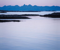 Calm water and distant mountains Stock Images