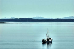 Calm Water, Fishing Boat, Juneau, Alaska, USA. In early May, as fishermen get ready to head out for the salmon fishing season in Alaska, workers are cleaning Royalty Free Stock Photos