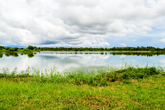 Calm water of lake, woods on other side and blue sky. Stock Photo