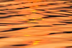 Calm water reflecting setting sun texture. Surface of water reflecting glowing orange sun Royalty Free Stock Photography