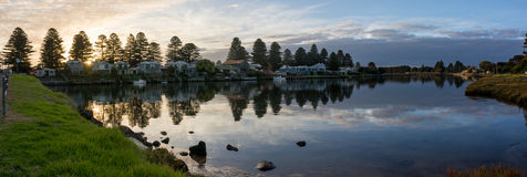 Calm water reflections in coastal town river at sunset. Panoramic view of river through small coastal town with trees, clouds and calm water reflections at Royalty Free Stock Photography