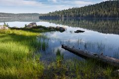 Calm water reflects shoreline trees on  vast waters of an  Alpine lake in Lassen Volcanic National Park on a clear  sunny day. Calm water reflects shoreline Stock Photo