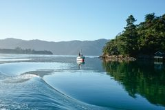 Calm water rippled by passing boat. Stock Photos