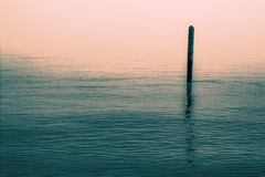 Calm water with solitary wooden post and reflection. Serene imag Stock Images