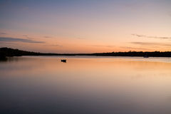 Calm Waters. The small boat moored in a peaceful, sheltered bay at dusk Royalty Free Stock Image
