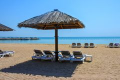 Calm Waters Beyond Thatched Roof Umbrella. Head for the seating underneath the thatched roof umbrella and admire the calm tropical blue waters of the Persian stock photography