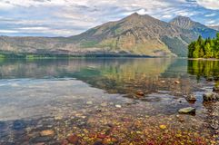 Mountains Reflected in the Waters of Lake MacDonald in Glacier National Park. The calm waters of Lake MacDonald reflect the mountains and the forest surrounding royalty free stock photography
