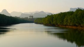 Sunset landscape of the river in mangrove forest against the mountains. The calm waters of the river reflect the blue sky in the evening with the green trees in stock footage