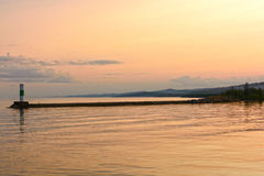 Calm Waters at Sunset on a Harbor Breakwater Royalty Free Stock Images